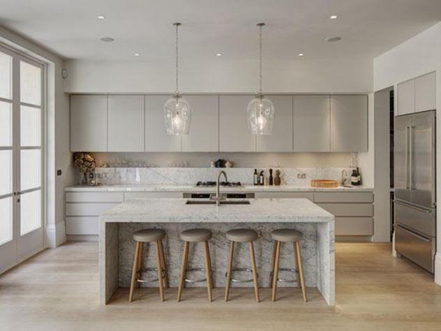 Cozinha monocromática fendi, com ilha central em granito, com quatro banquetas de madeira e assento fendi.