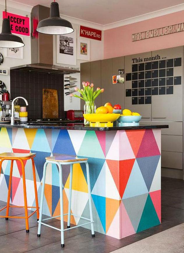 Nesta cozinha americana o balcão pintado com triângulos coloridos dá o tom alegre ao ambiente, que tem duas banquetas do mesmo modelo, porém em cores diferentes.
