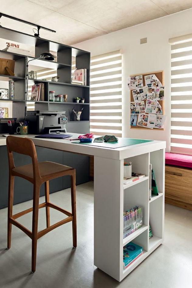 Home office organizado, com estante preta que ocupa toda a parede à esquerda e bancada de trabalho branca em forma de ilha, com banqueta de madeira.
