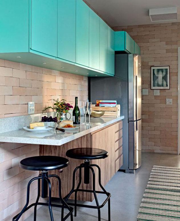 Cozinha estilo corredor, estreita e comprida. Paredes em tijolos aparentes, sem rejunte. Balcão para refeições com duas banquetas de ferro, em estilo industrial vintage. Armários aéreos em laca azul turquesa.