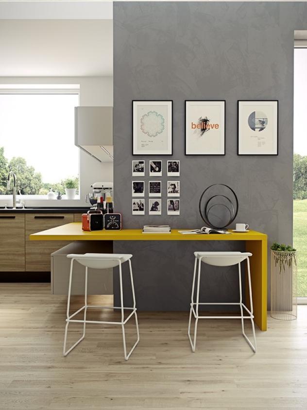 Nesta cozinha aberta, o balcão amarelo, único ponto de cor do ambiente, faz as vezes de mesa. Duas banquetas brancas se encaixam perfeitamente no móvel.