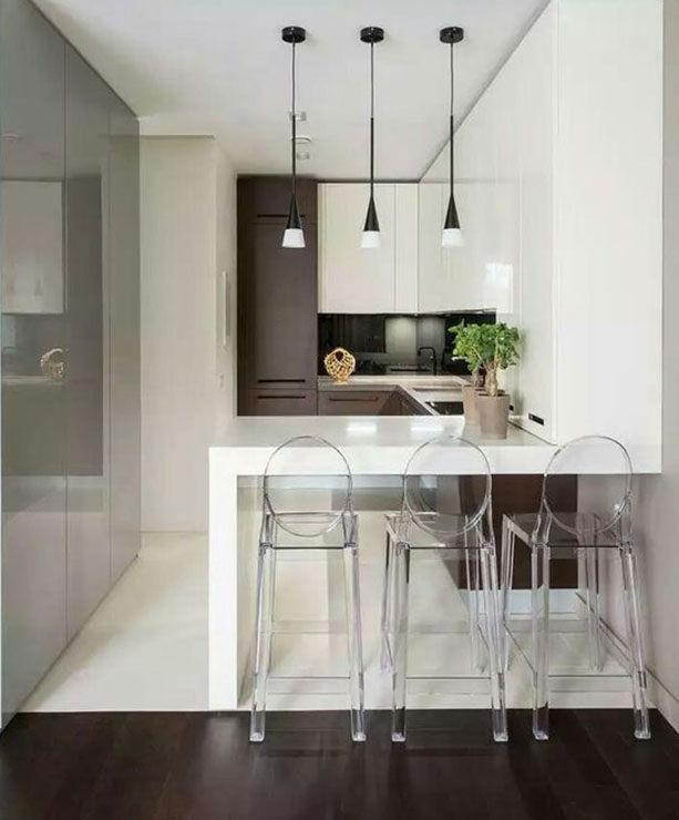 Cozinha minimalista, com predominância do branco, que aparece no chão, na bancada de silestone e em parte dos armários. As banqueta Iglo, de policarbonato transparente, contribuem para que o ambiente seja fluido e moderno.