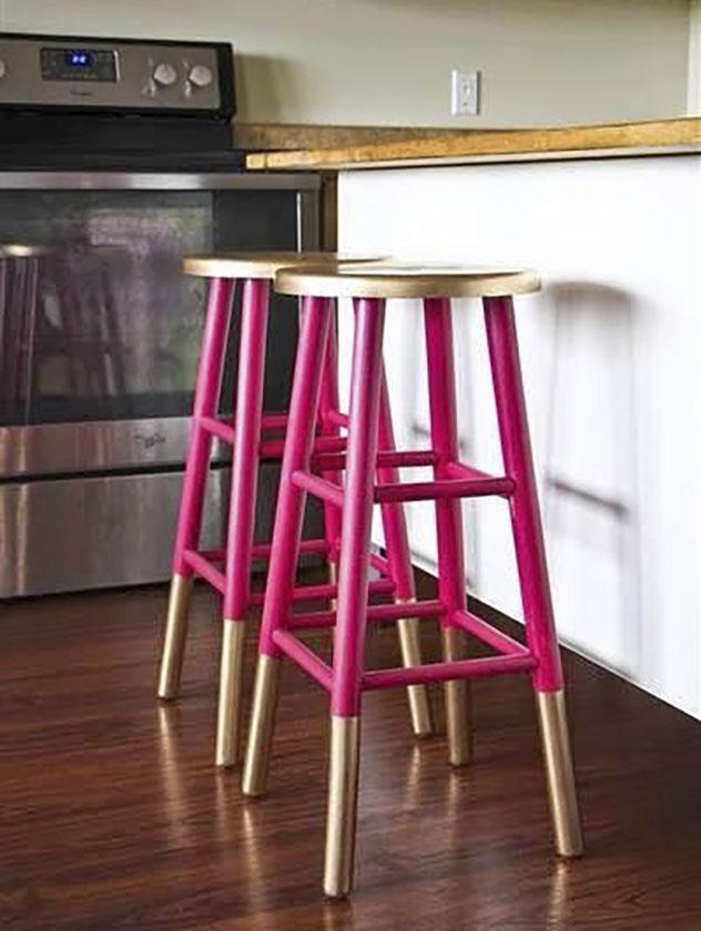 Duas banquetas de madeira, pintadas de pink, com pés e assentos dourados.